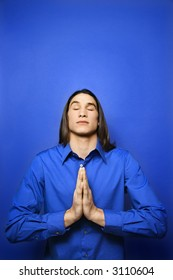 Portrait of Asian-American teen boy with palms pressed together in prayer position standing against blue background.
