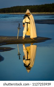 Portrait of assassin in white costume with the sword at the sea. He is posing near water with reflections on it. Sunset time. Isolated.