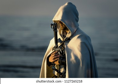 Portrait of assassin in white costume with the sword at the sea. He is posing near water during sunset, soft light.