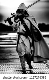 Portrait of assassin in white costume with the sword at the sea with skull instead of face. Black and white image.