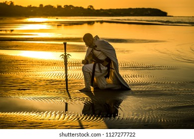 Portrait of assassin in white costume with the sword at the sea. He is posing at the sea during beautiful sunset. Yellow, soft light.