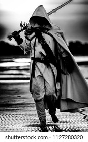 Portrait of assassin in white costume with the sword at the sea. Black and white image.