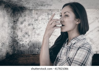 Portrait of an asthmatic woman against image of room corner
