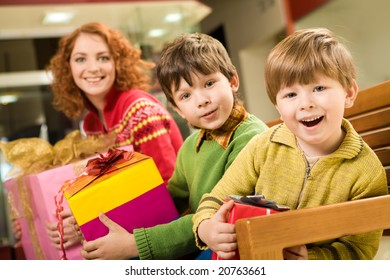 Portrait of astonished brothers with nice gifts sitting in supermarket with their mother behind