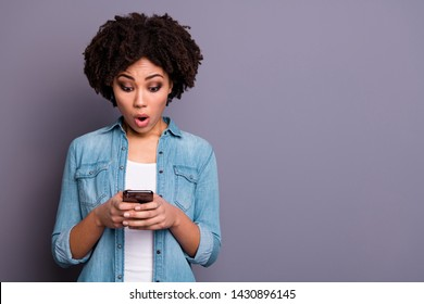 Portrait of astonished funny funky lady hold hand use user gadget look news feed impressed horrible information fear stress depressed dressed jeans outfit isolated grey background