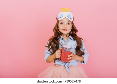 Portrait astonished joyful little girl holding glass with juice, expressing to camera isolated on pink background. Funny cute kid in princess mask celebrating, having fun in happy childhood
