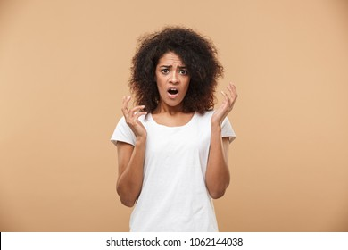 Portrait of an astonished young african woman looking at camera with an open mouth isolated over beige background