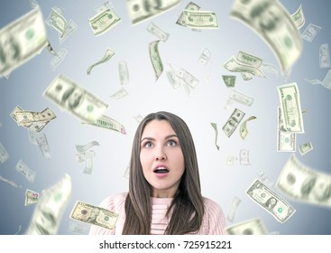 Portrait of an astonished young woman looking upwards. She is wearing a pink sweater and standing under a dollar rain. Gray wall background