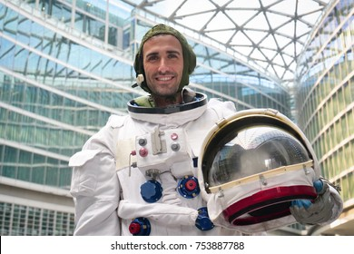 Portrait of an astronaut just landed and walking for the first time in town and looks around in both the metro and open air in the city. Concept of: freedom, ambition, new planets, exploration, surrea