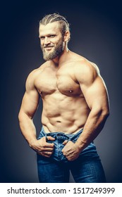 Portrait of a athleltic muscular bearded man posing on a grey background