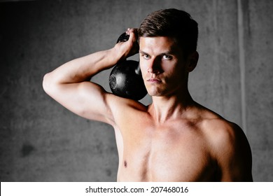 Portrait of an athlete with a kettlebell on his shoulder