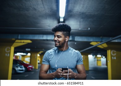Portrait of athlete man using mobile phone and listening to the music in the underground car parking.