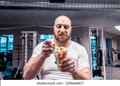 portrait of athlete while eating an ice cream on break after training in the gym
