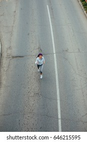 Portrait of an athlete woman running on the road.