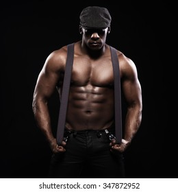 Portrait of an athletic african american man topless. Only in suspenders and cap