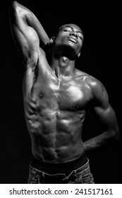 Portrait of an athletic black man on black background. Black and white
