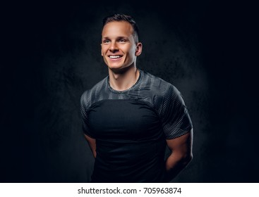 Portrait of an athletic fitness male dressed in a sportswear over grey vignette background.