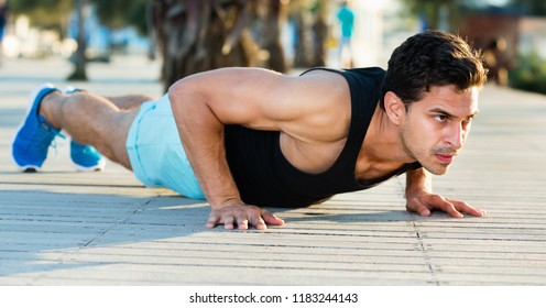 Portrait of athletic happy positive  man training on beach doing press up exercises