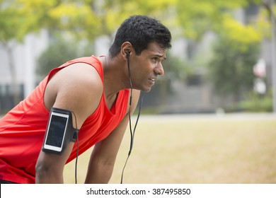 Portrait of athletic Indian man resting after urban run through city streets. Asian male runner taking break standing relaxing.