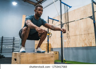 Portrait of an athletic man doing box jump exercise. Crossfit, sport and healthy lifestyle concept.
