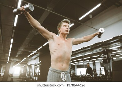 Portrait of athletic man exercising with dumbbells in gym. Athlete man exercises with training dumbbells at biceps brachii muscles in fitness gym