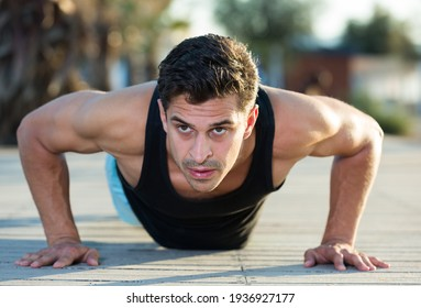 Portrait of athletic man training on beach doing press up exercises