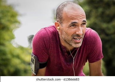 Portrait of athletic mature man after run. Handsome senior man resting after jog at the park on a sunny day. Sweaty multiethnic man listening to music while jogging.