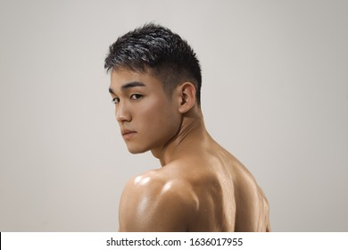 Portrait of athletic muscular Asian man standing on a grey background. Attractive confident young man looking away. Male Fashion shot, muscular Asian guy