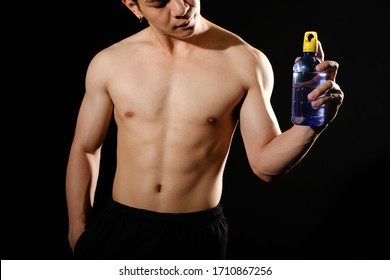 portrait of athletic muscular bodybuilder man with naked torso six pack abs holding water bottle. fitness workout concept