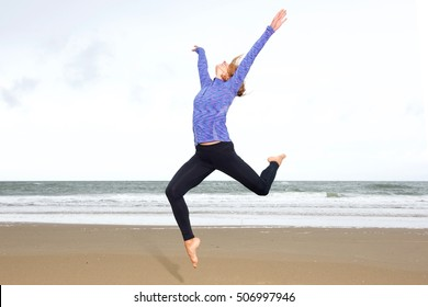 Portrait of athletic woman leaping in air with arms outstretched