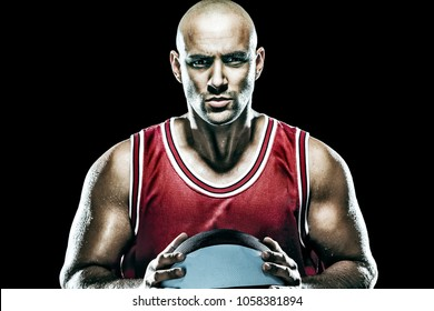 Portrait of a athletic young baskeball player wearing red over black background holding a basketball