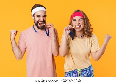 Portrait of athletic young happy couple wearing headbands celebrating victory with award medals isolated over yellow background
