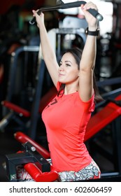 Portrait of athletic young woman doing exercises for back muscles on simulator machine at gym