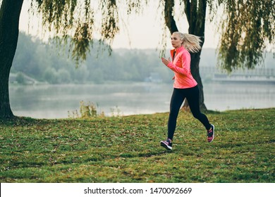 Portrait of athletic young woman running near lake during morning jog on sunny autumn day