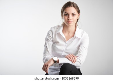 Portrait of attracive young businesswoman wearing white shirt and looking at camera while sitting at isolated white background.