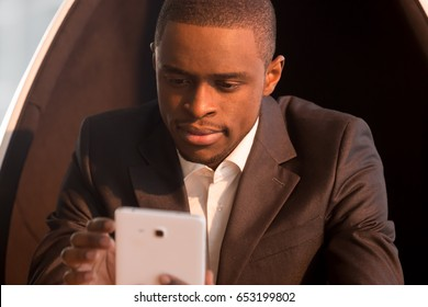 Portrait of attractive african american businessman holding tablet, sitting in chair, organizing scheduling meetings, using business apps, online banking, reading e-book, stay in touch, mobile office