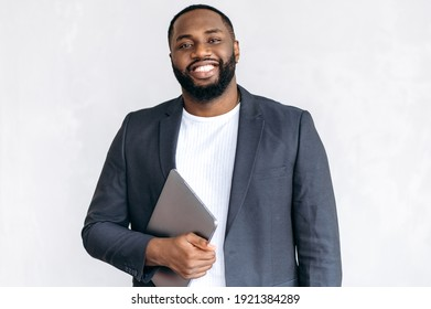 Portrait of an attractive African American male entrepreneur, freelancer or student in stylish suit, standing in the office holding laptop, looking and smiling friendly at the camera