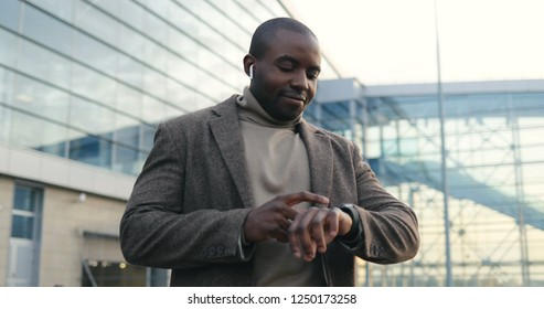 Portrait of the attractive African American young man in business style and headphones looking at the watch on a hand while waiting for somebody at the big glass building. Outdoor.