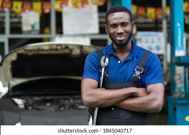 Portrait of attractive African man arm cross look camera and big wrench tools in hand. Expertise mechanic working in automobile repair garage.