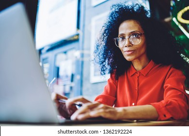 Portrait of attractive afro american copywriter working remotely with modern netbook in cafe interior,black woman in eyeglasses looking at camera while waiting for online answer from internet provider