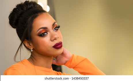 Portrait of attractive afro american young woman with fashion luxury makeup orange-coloured shades and her hair scraped back into high bun. Perfect Skin. Long eyelashes. Big lush beautiful lips.