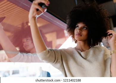 Portrait of attractive afro woman taking selfie portrait at the coffee shop
