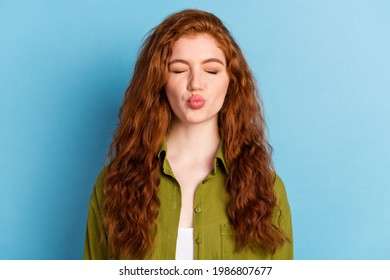 Portrait of attractive amorous shy long-haired girl sending air kiss romance isolated over pastel blue color background