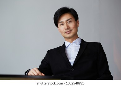 Portrait of attractive asian businessman on gray wall background