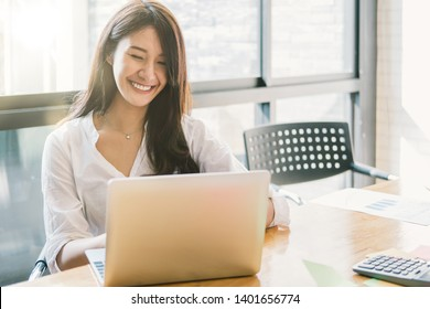 Portrait Of Attractive Asian Businesswoman Working On Laptop for marketing plan