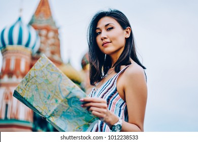 Portrait of attractive asian female tourist standing with map near ancient notable place in Moscow, charming girl looking at camera satisfied with getting to destination St. Basil's Cathedral