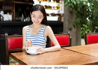 Portrait of attractive Asian girl enjoying cup of hot coffee in the morning.