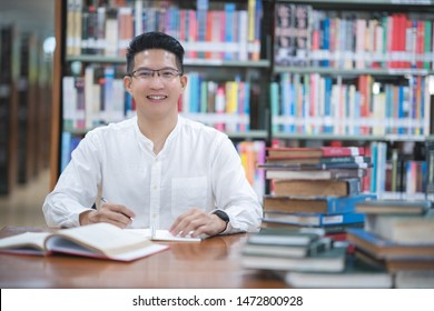 Portrait attractive  Asian man smiling in the library room,Man people lifestyle and education concept