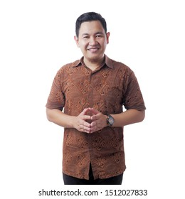 Portrait of attractive Asian man wearing batik shirt smiling isolated on white