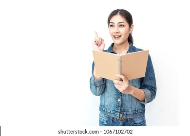 Portrait of attractive asian student ( woman ) standing holding reading a book with copy space over white background with finger point up. Education test exam thinking concept